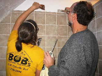 Here KRisten and Bob of www.renovationsredoak.com finish some tile work.