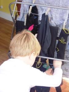 This young man is hanging out damp laundry to dry. He is doing a green chore, which is common in Ireland. Such a simple chore for a child that brings complex benefits, such as self-esteem, self-confidence, skill, connection to family and self-discipline. These are priceless. All through family meetings, family chores and encouragement. Mom does the chores with the kids. that helps enormously.